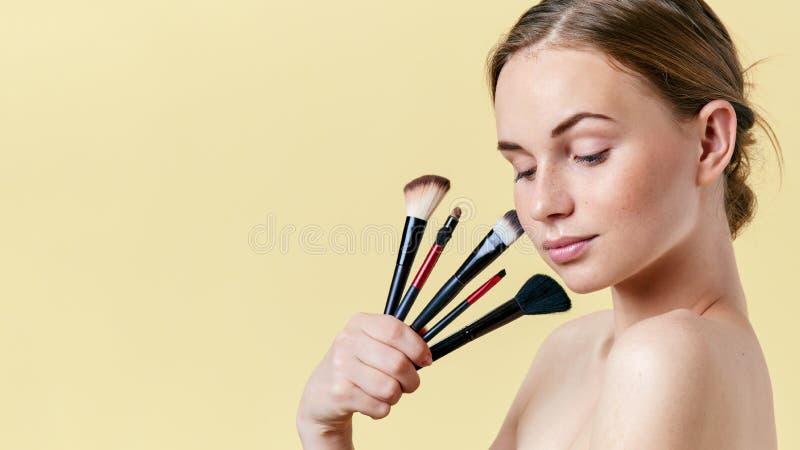 L'adolescente grazioso della testarossa con le lentiggini, guardando giù, giudicanti diverso compone le spazzole Modello con truc immagini stock