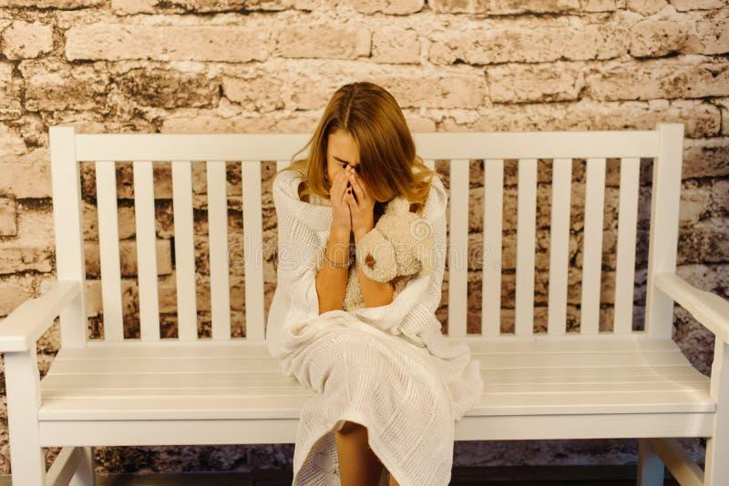 L'adolescente gridante è avvolto nel plaid tricottato mentre si siede sul banco fotografia stock