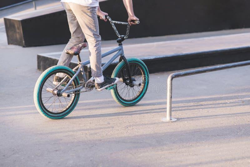 l'adolescente guida una bici blu di BMX su un parco del pattino e si accinge a per fare un trucco Un giovane guida una bici di BM immagini stock libere da diritti