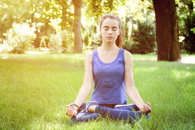 L'adolescente medita in natura fotografia stock