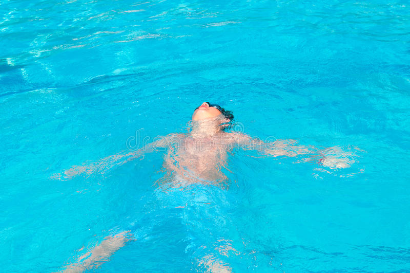L'adolescente nuota in raggruppamento fotografia stock