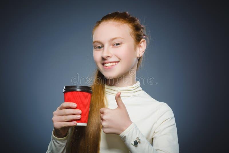 L'adolescente offre la tasse de café rouge d'isolement sur le fond gris image stock