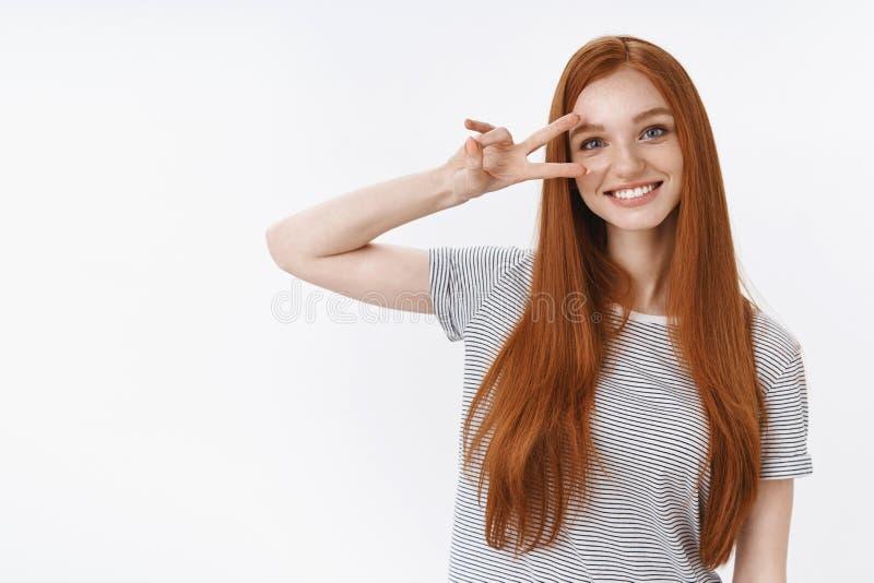 L'adolescente ottimista sveglio positivo della testarossa si diverte mostrando l'occhio del segno della discoteca della tenuta di fotografia stock libera da diritti