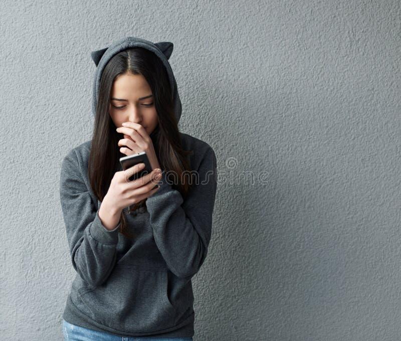 L'adolescente premuroso scrive SMS immagine stock