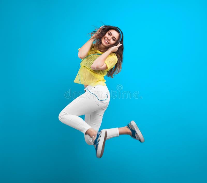 L'adolescente sautant tenant des écouteurs photos libres de droits