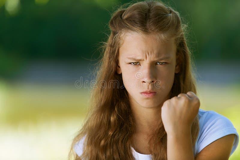 L'adolescente severo agita il suo pugno fotografia stock