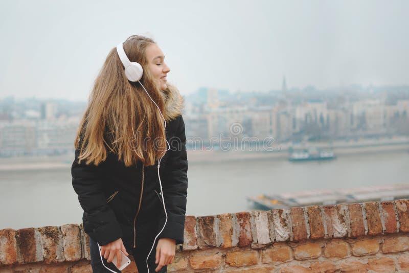L'adolescente sorridente allegro gode di di ascoltare la musica immagini stock libere da diritti