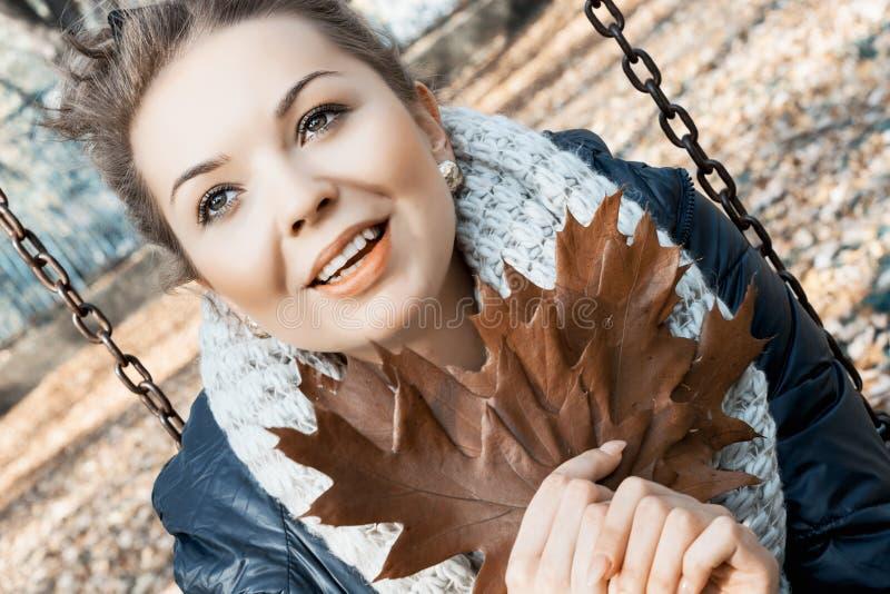 L'adolescente sorridente con la quercia marrone lascia nelle mani fotografie stock