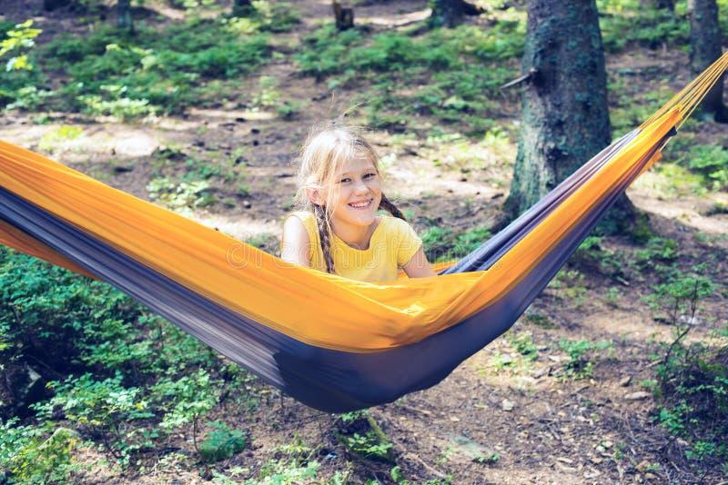 L'adolescente sorridente si rilassa in un'amaca fotografie stock