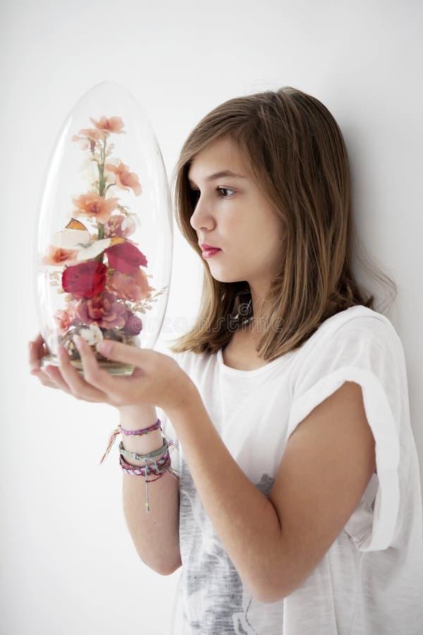L'adolescente sta guardando un barattolo di vetro immagine stock libera da diritti