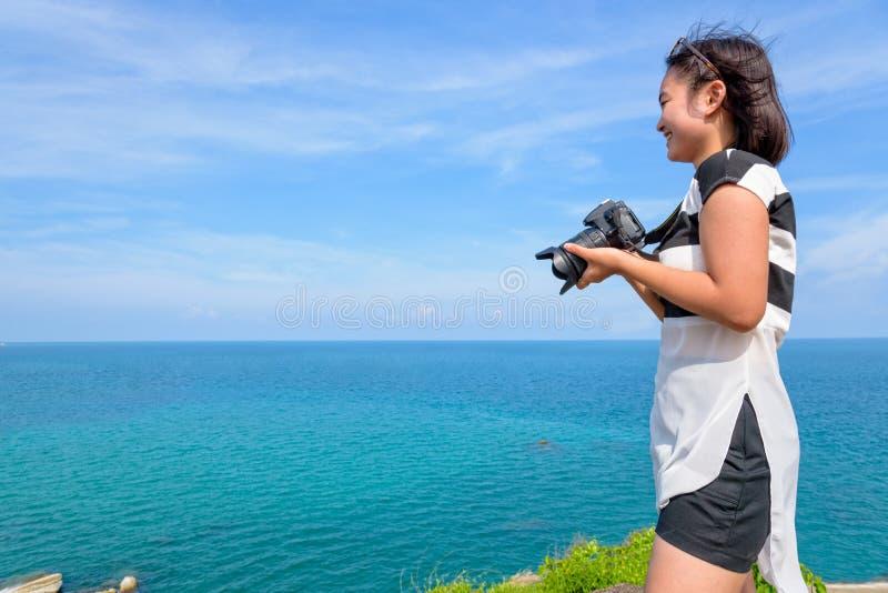 L'adolescente tient l'appareil-photo sur la haute photos libres de droits