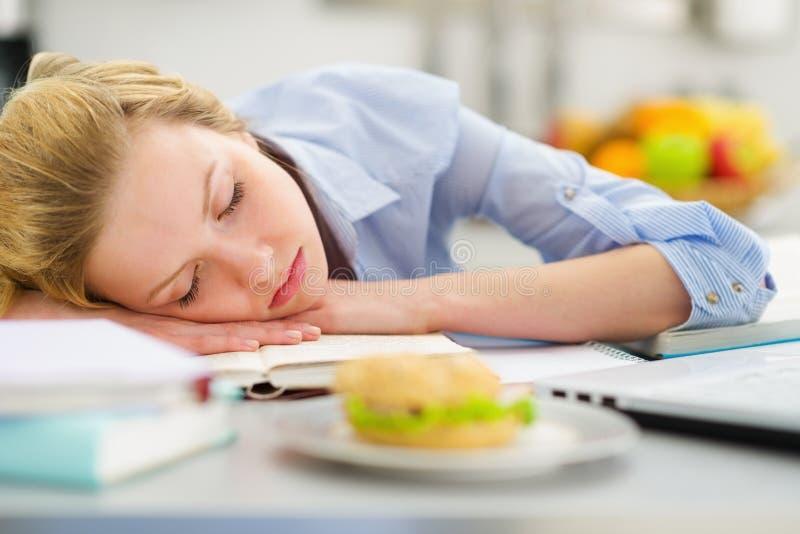 L'adolescente tombent endormi tout en étudiant dans la cuisine images stock