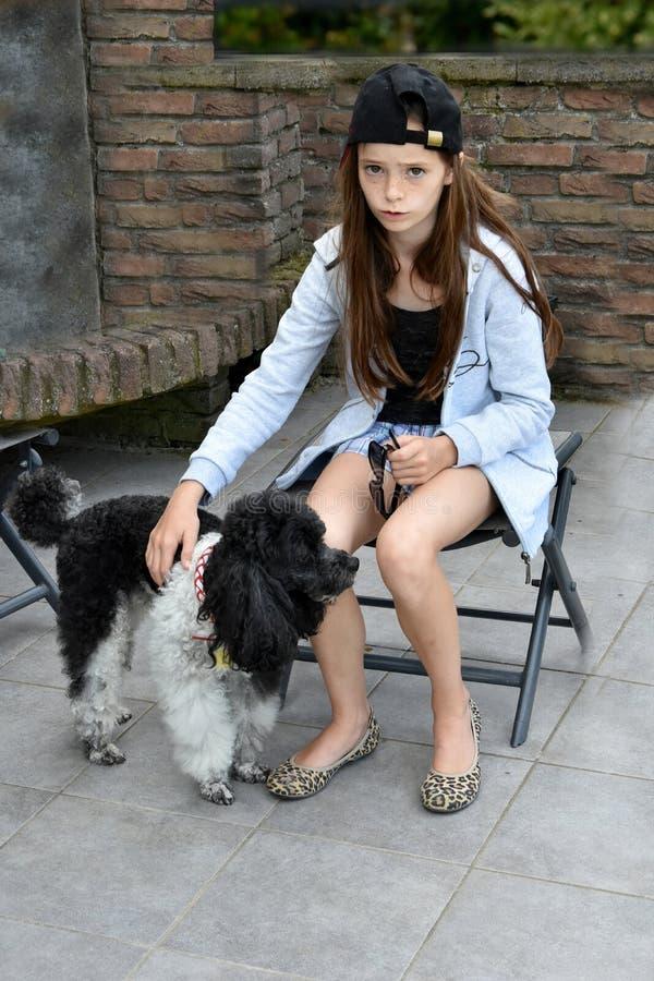 L'adolescente triste est soulagée par son petit chien de caniche photos libres de droits