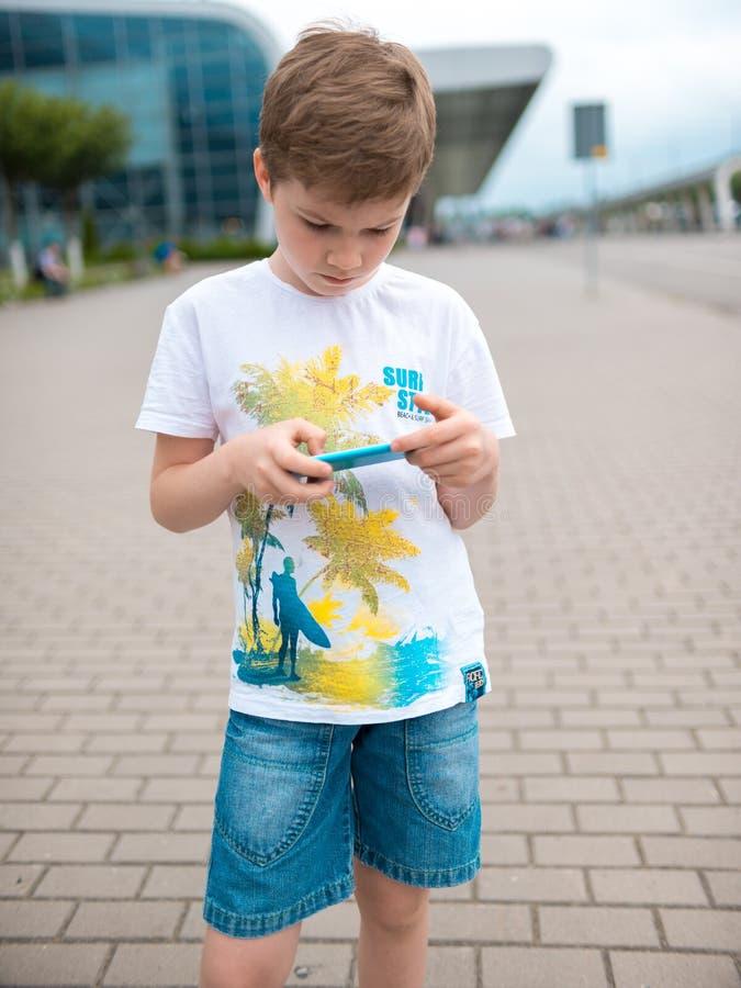 L'adolescente, vestito in maglietta bianca, si siede all'aperto sul pattino e sullo smartphone di usi, aggeggio digitale, giochi  immagini stock