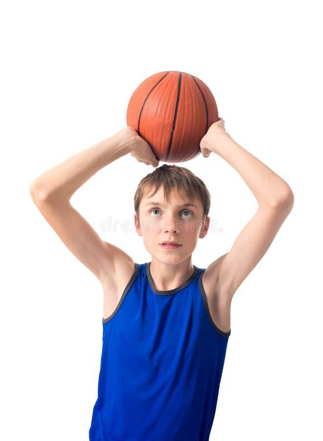 L'adolescente vuole gettare una palla per pallacanestro Isolato su priorità bassa bianca immagine stock libera da diritti
