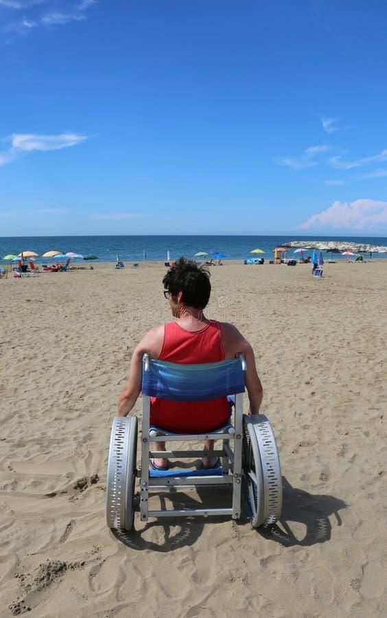 L'adulte handicapé regarde la mer d'un fauteuil roulant image libre de droits