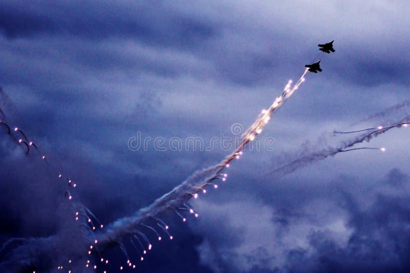 L'aereo da caccia moderno sta infornando un insieme dei chiarori sul cielo blu Condensazione della nuvola sulle ali fotografia stock libera da diritti