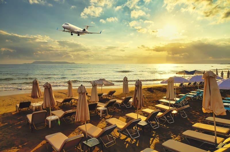 L'aereo di affare privato su atterraggio sorvola la spiaggia sabbiosa con le chaise-lounge del sole sui precedenti del tramonto,  immagine stock