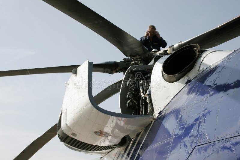 L'aeronautica Enginerr meccanico sta esaminando il motore dell'elicottero immagine stock libera da diritti