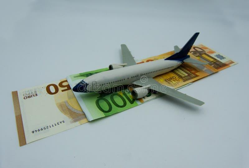 L'aeroplano bianco decolla su un mucchio di euro banconote Concetto di aviazione fotografia stock