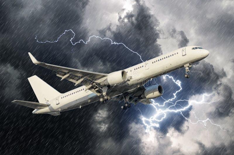 L'aeroplano bianco del passeggero decolla durante il fulmine di temporale di pioggia, il maltempo immagini stock libere da diritti
