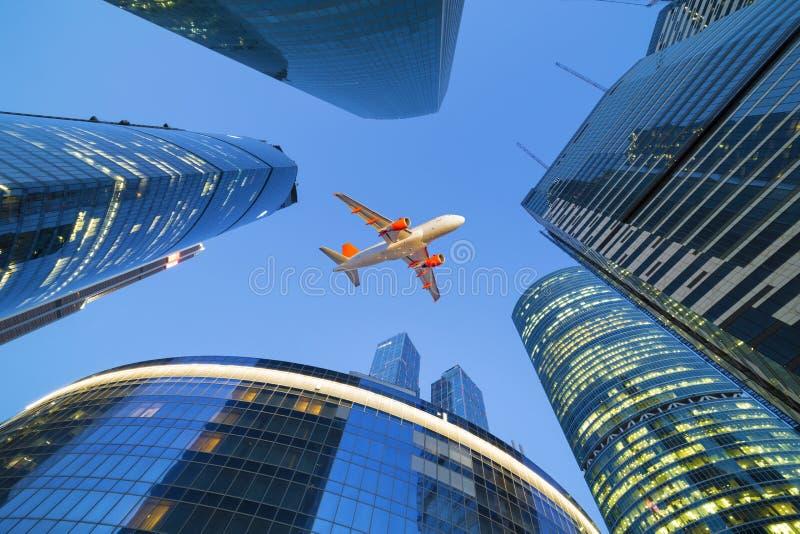 L'aeroplano dell'aereo di linea vola sopra i grattacieli fotografia stock