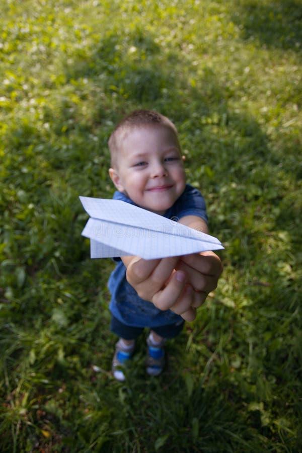 L'aeroplano di carta in bambino passa il primo piano Il ragazzo del bambino 4 anni che tengono gli origami spiana in parco o in g immagini stock