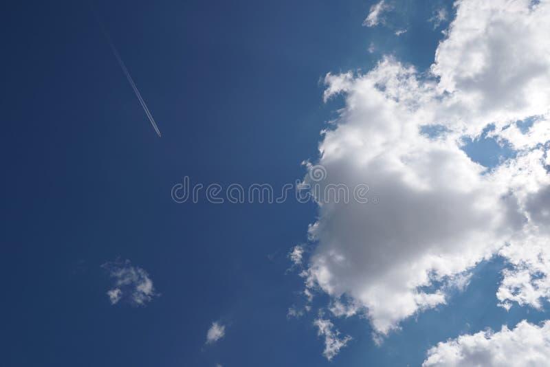 L'aeroplano sta muovendosi attraverso il cielo blu con le nuvole alla marinara fotografia stock libera da diritti