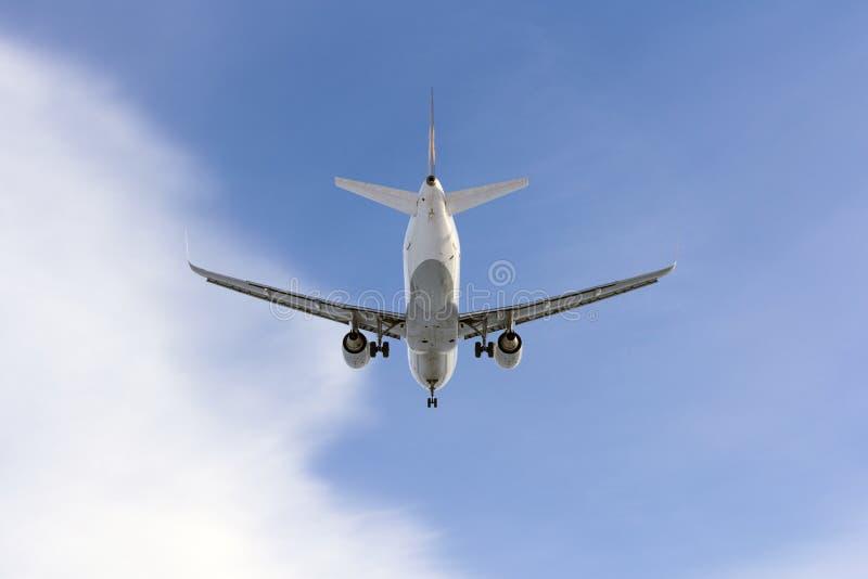 L'aeroplano vola contro un fondo della nuvola bianca fotografia stock