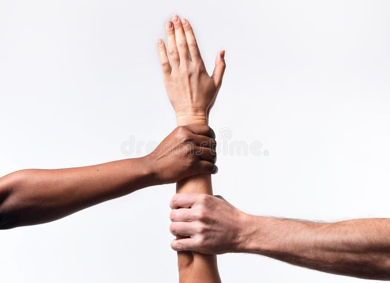 L'africain noir américain et les mains caucasiennes tenant la peau blanche arment dans l'unité du monde photographie stock libre de droits