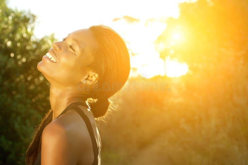 L'afro-américain de sourire folâtre la femme se tenant dehors images stock