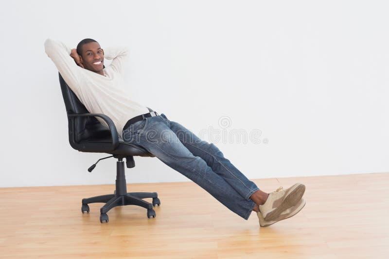 L'afro sorridente equipaggia la seduta sulla sedia dell'ufficio in una stanza vuota immagine stock