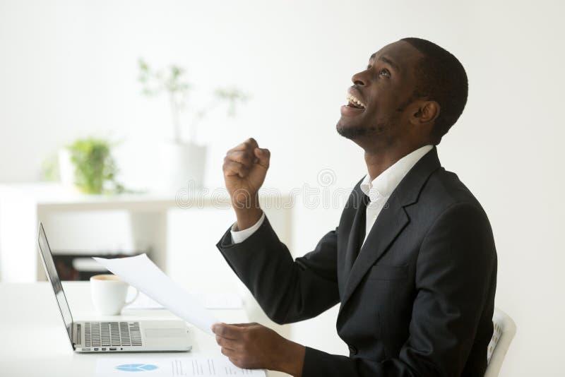 L'afroamericano emozionante soddisfatto con la buona lettura di risultati ha lasciato immagini stock libere da diritti