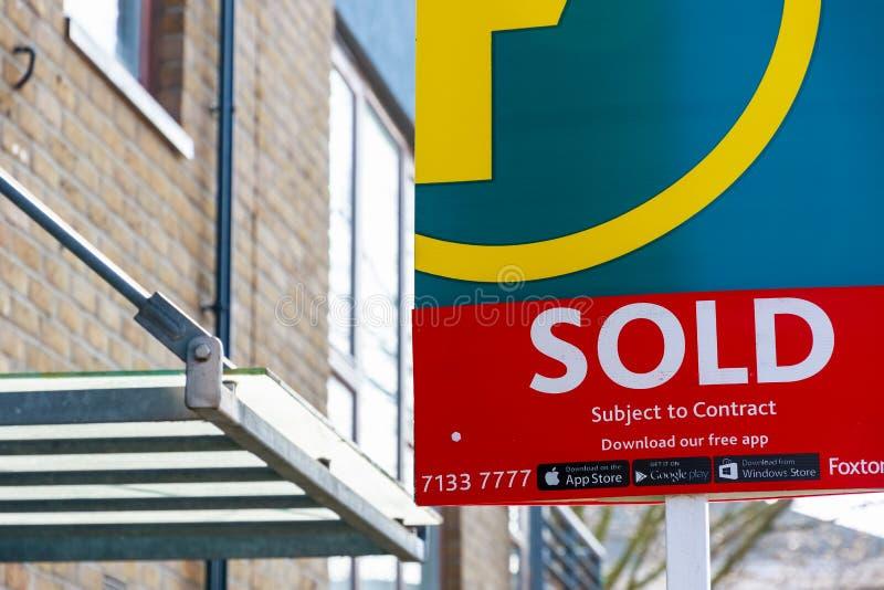 L'agence immobilière a vendu le signe en dehors d'une maison urbaine anglaise image libre de droits