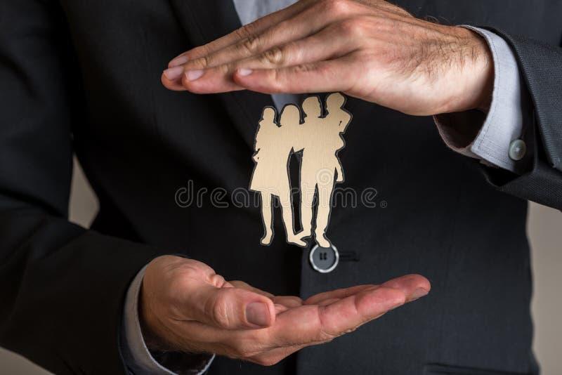 L'agent d'assurance faisant le geste protecteur autour d'un papier a coupé le sil photographie stock libre de droits
