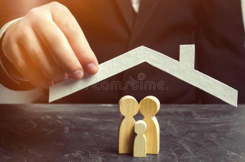 L'agent d'assurance tient une maison au-dessus de la famille Le concept de l'assurance de la vie de famille et de la propriété So photos stock