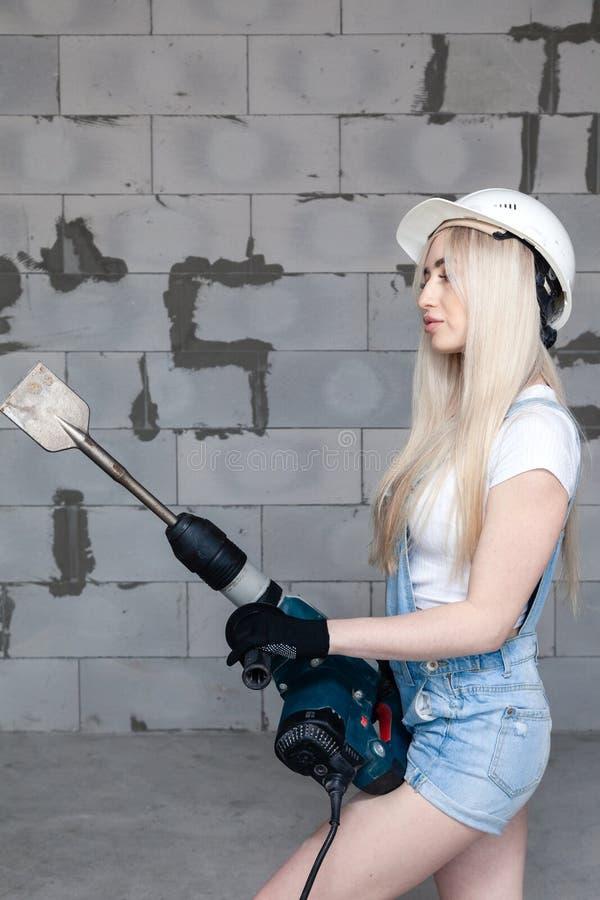 L'agent de maîtrise blond de fille de plan rapproché dans le casque blanc de construction tenant le perforateur professionnel, fo images libres de droits