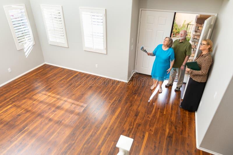L'agent femelle Showing Senior Adult de Real Estate couplent une nouvelle maison photo libre de droits