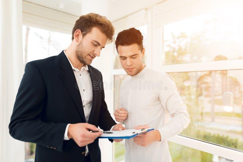 L'agent immobilier discute avec le client les conditions pour acheter ou vendre les immobiliers photo libre de droits