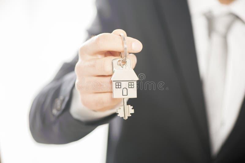 L'agent immobilier donnant des clés de maison sur une maison argentée a formé le keychain photographie stock