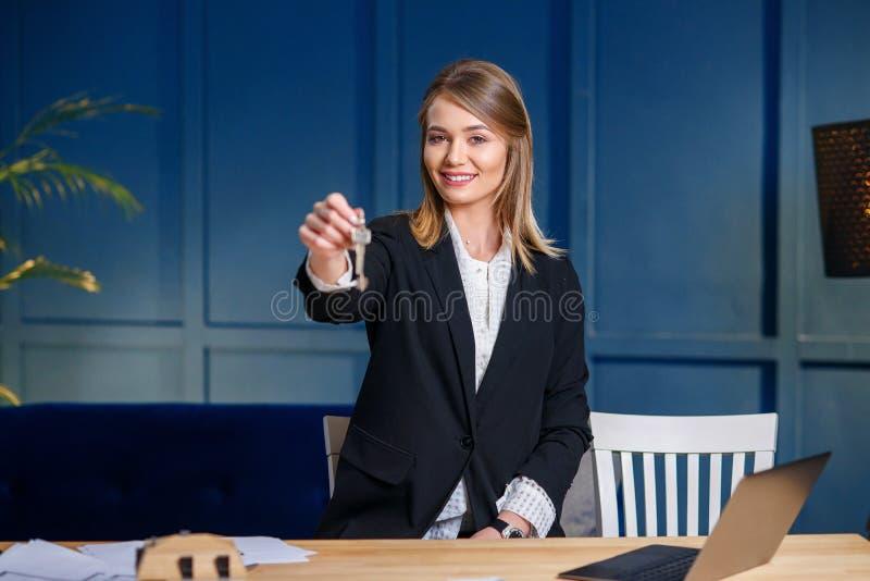 L'agent immobilier femelle de sourire donne des cl?s sur le fond bleu photos libres de droits