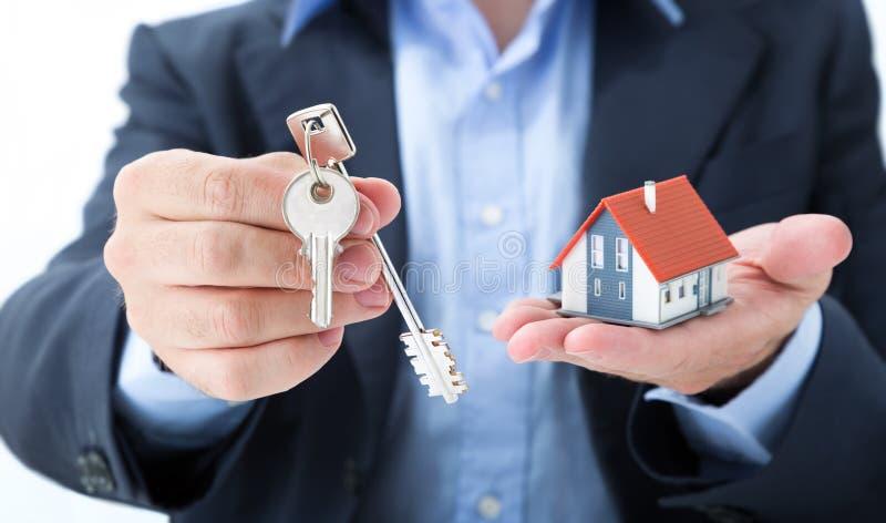 L'agent immobilier livrent avec des clés de maison image stock