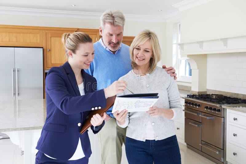 L'agent immobilier montre les couples mûrs autour de la Chambre images stock
