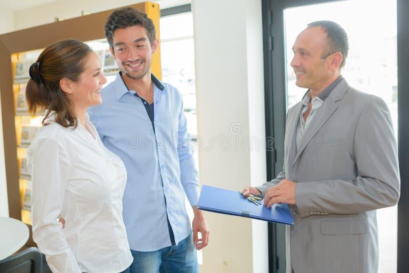L'agent immobilier s'est tenu avec de jeunes couples images stock