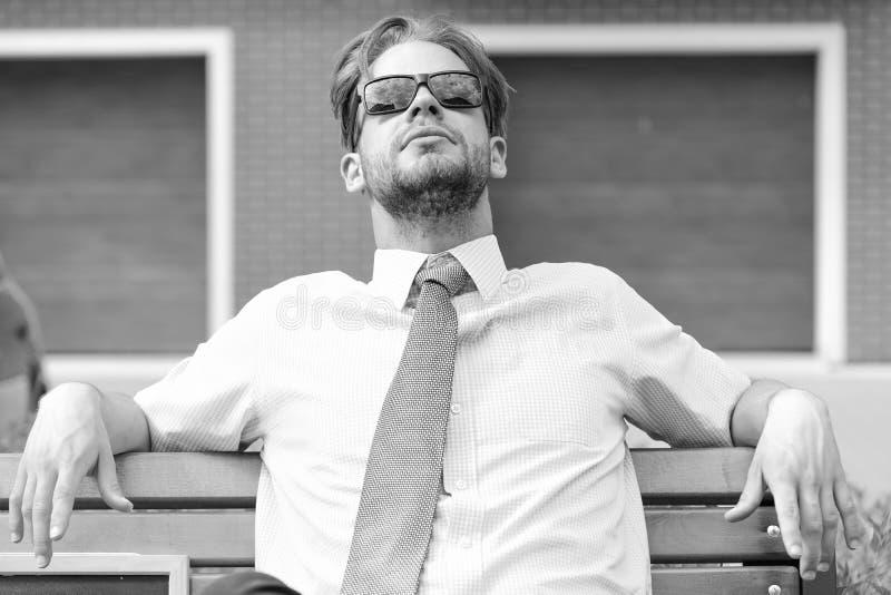 L'agent immobilier se repose sur le banc et détend après jour ouvrable Homme d'affaires adulte recherchant les lunettes de soleil photos libres de droits