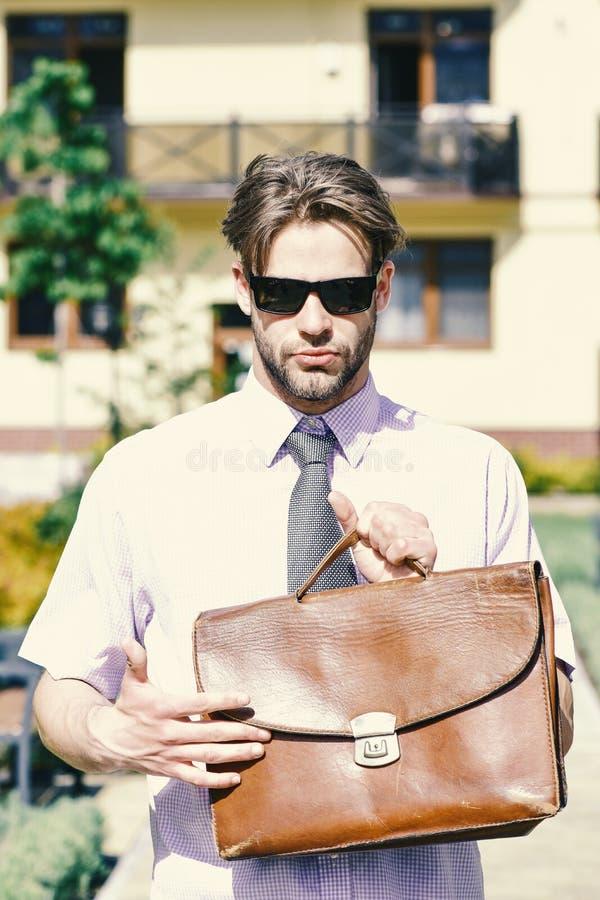 L'agent immobilier tient la serviette Jeune homme dans la cour de la maison de rapport le jour ensoleillé photos libres de droits