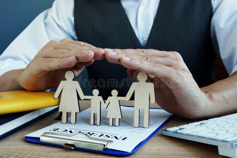 L'agent protège des chiffres de famille La police d'assurance-vie sur un bureau images stock
