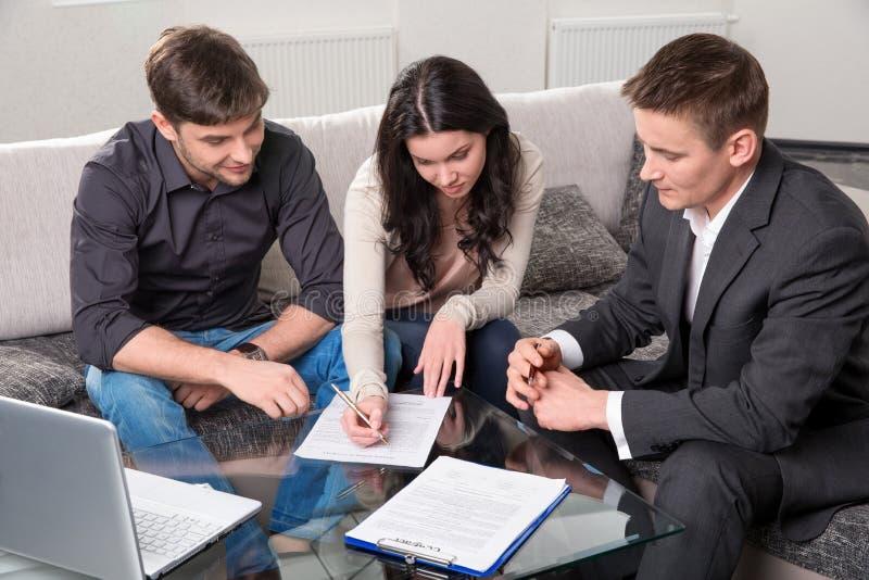 L'agente consiglia le coppie, firmanti i documenti fotografia stock libera da diritti