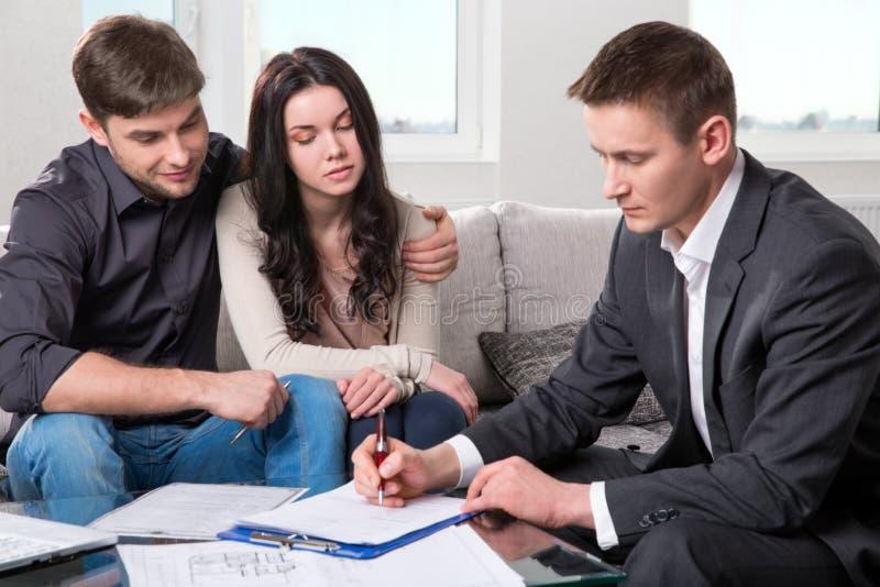 L'agente consiglia le coppie, firmanti i documenti immagini stock