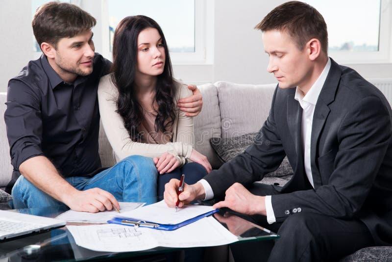 L'agente consiglia le coppie, firmanti i documenti immagini stock libere da diritti